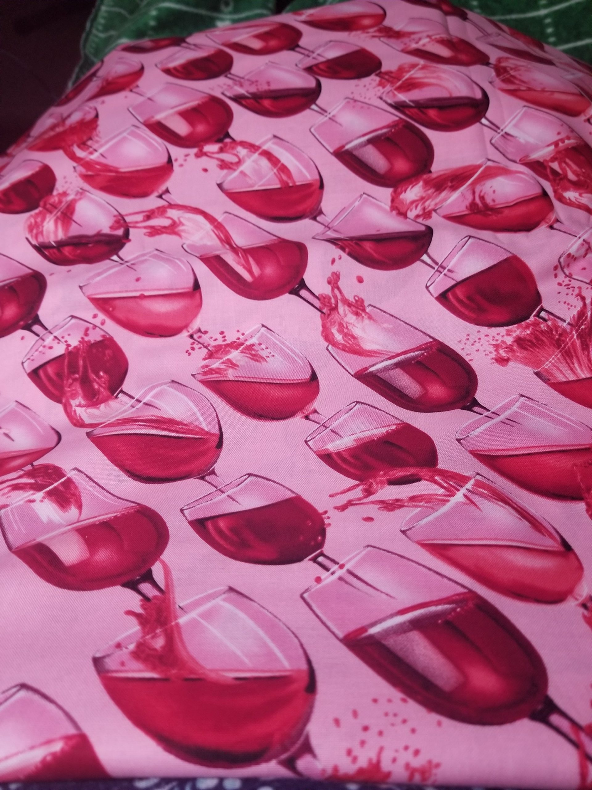 KANVAS Cheers fabric pink background with cherry red wine glasses in diagonal pattern