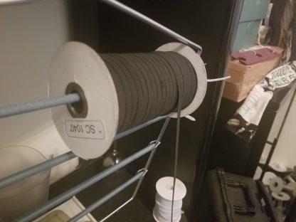 """144 yard spool of 1/4"""" black elastic being cut"""
